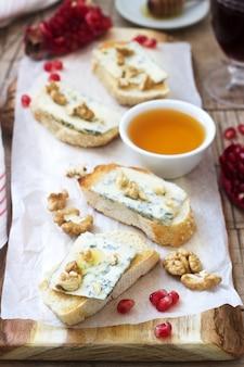 Бутерброды с голубым сыром, гранатом, медом и орехами подаются с красным вином. деревенский стиль
