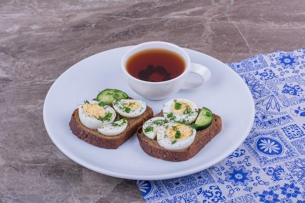 Бутерброды с вареными яйцами и зеленью за чашкой чая.