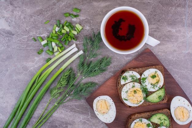 Panini con uova sode ed erbe aromatiche con una tazza di tè.