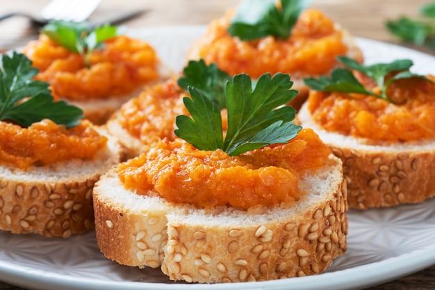 パンズッキーニキャビアトマト玉ねぎのサンドイッチ。自家製ベジタリアン料理。野菜の煮込み缶詰。木製の背景をクローズアップ