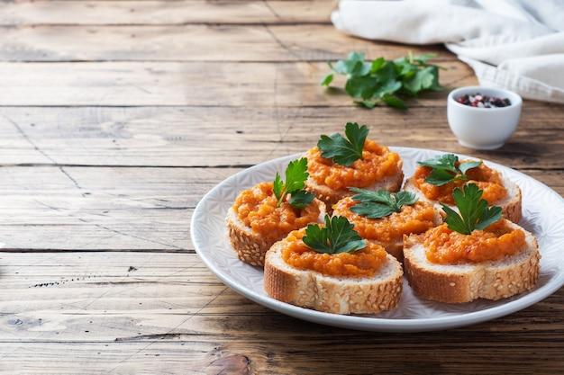 パンズッキーニキャビアトマト玉ねぎのサンドイッチ。自家製ベジタリアン料理。野菜の煮込み缶詰。木製の背景のコピースペース