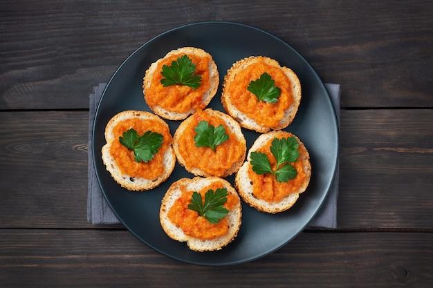 パンズッキーニキャビアトマト玉ねぎのサンドイッチ。自家製ベジタリアン料理。野菜の煮込み缶詰。木製の背景上面図、コピースペース