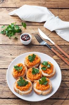 パンズッキーニキャビアトマト玉ねぎのサンドイッチ。自家製ベジタリアン料理。野菜の煮込み缶詰。木製の背景