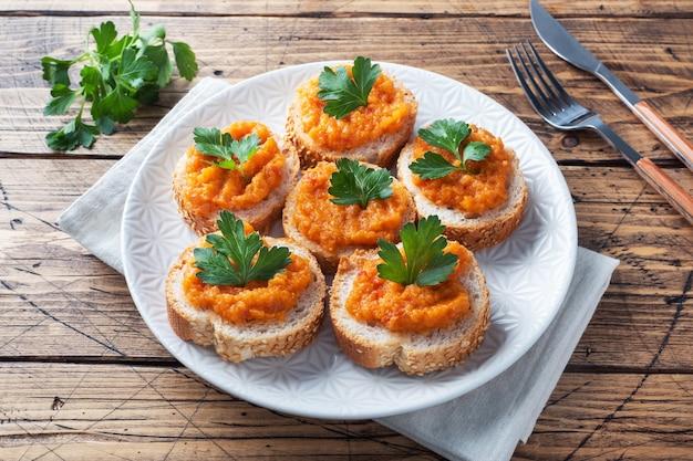 빵 호박 캐비어 토마토 양파와 샌드위치입니다. 집에서 만든 채식 음식. 통조림 야채 조림. 나무 배경