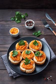 パン ズッキーニ キャビア トマト 玉ねぎのサンドイッチ。自家製ベジタリアン料理。野菜の煮込み缶詰。木の表面のコピースペース