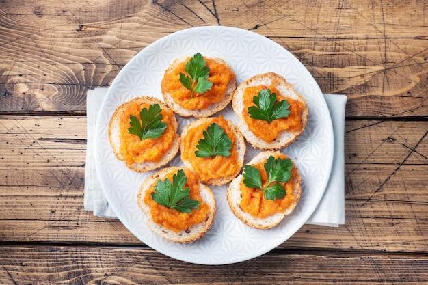 パン ズッキーニ キャビア トマト 玉ねぎのサンドイッチ。自家製ベジタリアン料理。野菜の煮込み缶詰。木の表面のトップ ビュー、コピー スペース