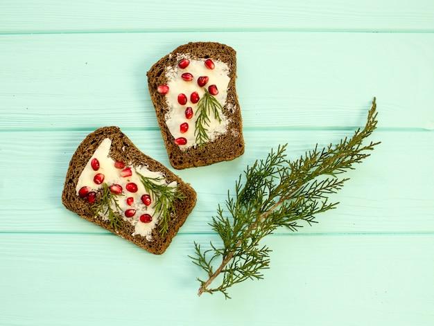 Бутерброды с маслом и ягодами граната на фоне бирюзы