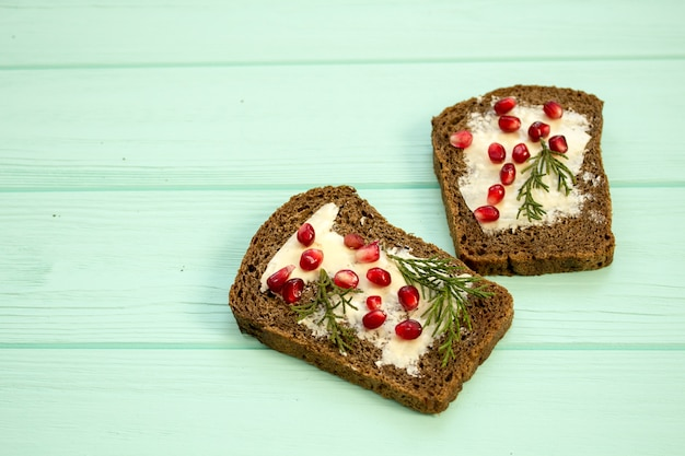 Sandwiches with butter and berries pomegranate on a turquoise background