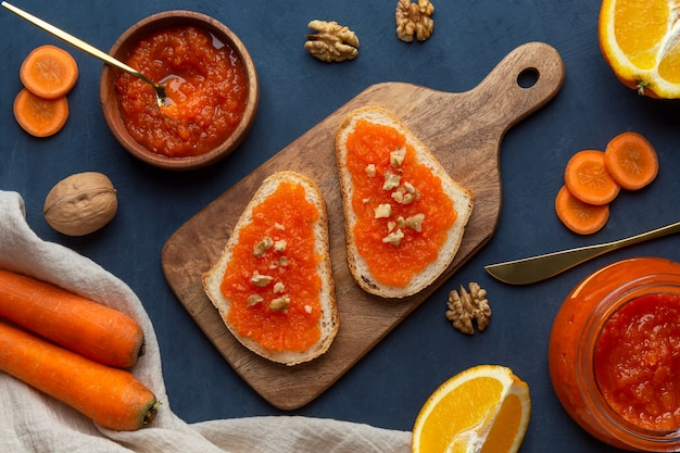 Sandwiches with carrot jam and nuts on a cutting board on a dark surface