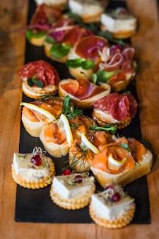 Бутерброды с сыром, рыбой, салями, зеленью и лимоном. выборочный фокус