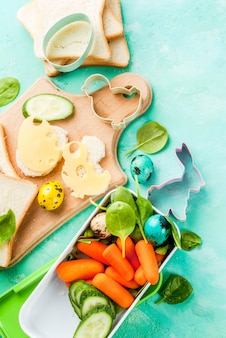 Sandwiches with cheese and fresh vegetables on light blue table
