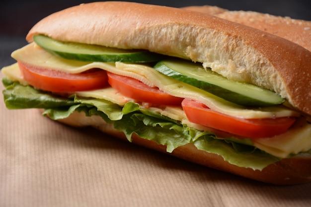 Бутерброды с сыром, листьями салата, помидорами и луком на темном фоне