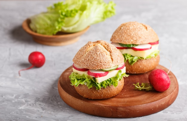 Sandwiches with cheese, radish, lettuce and cucumber on wooden board