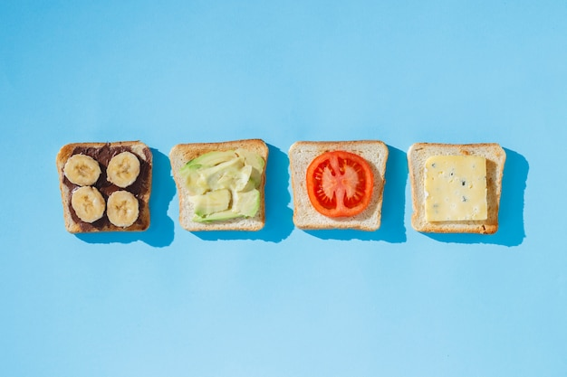 Sandwiches with cheese, tomato, banana and avocado on a blue surface.  flat lay, top view.