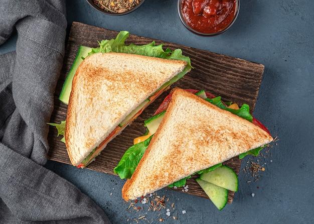 濃い青の背景に木の板にチーズ野菜とハムのサンドイッチ