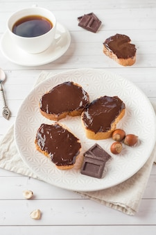 Sandwiches with chocolate hazelnut spread on the plate. cup of coffee on the table.