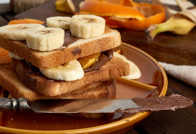 Sandwiches with chocolate paste and banana slices on a plate