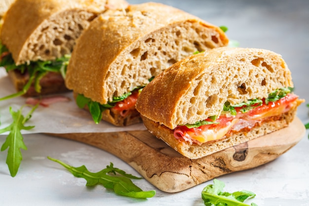 Sandwiches with ciabatta, ham and vegetables on a wooden board