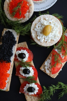 Sandwiches with cracker bread, caviar and vegetables. top view.