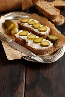 木製のテーブルにクリームチーズと塩漬けキュウリのサンドイッチ