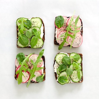 Sandwiches with cream cheese, fresh cucumber, radish, chia seeds and arugula on white paper. overhead food shots. flat lay