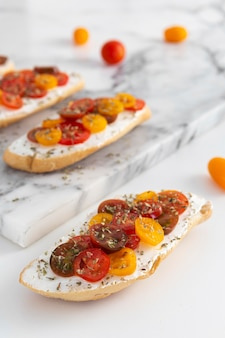 Sandwiches with cream cheese and tomatoes on marble counter