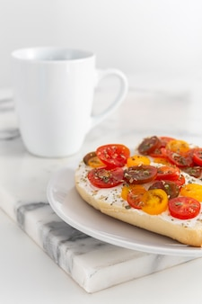 Sandwiches with cream cheese and tomatoes with mug
