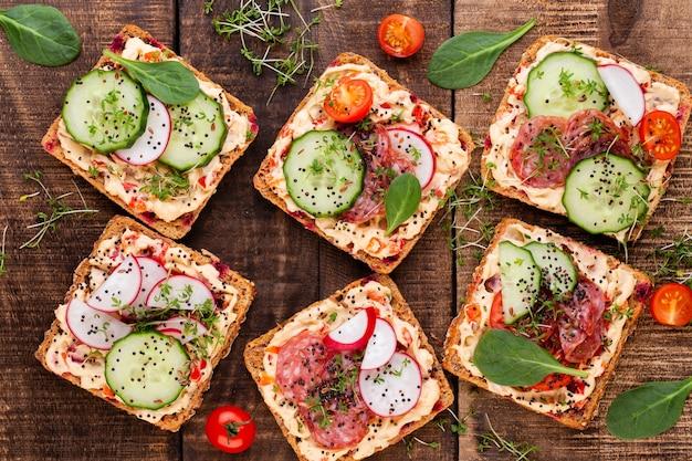Бутерброды со сливочным сыром, овощами и салями. бутерброды с огурцом, редисом, помидорами, салями на сером фоне, вид сверху. плоская планировка.