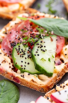 Sandwiches with cream cheese, vegetables and salami. sandwiches with cucumber, radish, tomatoes, salami on a gray background, top view. flat lay.