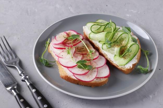 회색 접시에 오이, 무, 완두콩 마이크로 그린 샌드위치