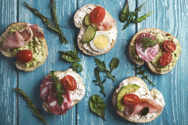 Бутерброды с творогом и овощами и колбасой на деревянных фоне.