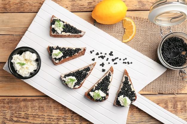 Бутерброды с вкусной черной икрой и творогом на деревянной доске