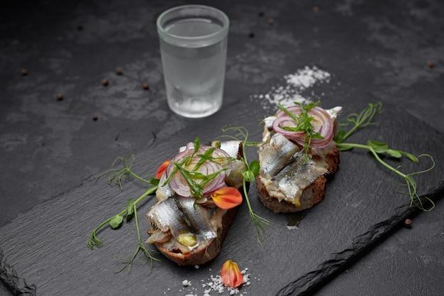 Бутерброды с тюлем рыбы на черном фоне. брускетты, водка, стекло