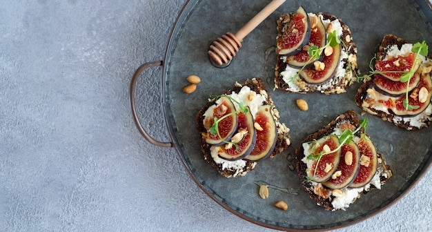 Sandwiches with fresh figs, cream cheese, nuts and honey on tray top view