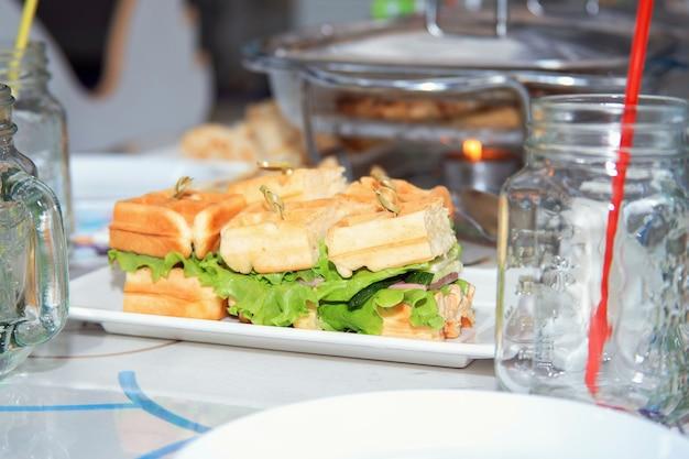 新鮮なグリーンサラダとキュウリのサンドイッチ。お祝いのテーブルセッティング