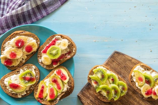 푸른 나무 배경에 과일 크림 바나나 사과와 키위가 있는 샌드위치 적절한 영양