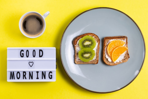 Sandwiches with fruits and cream cheese on a plate with a coffee