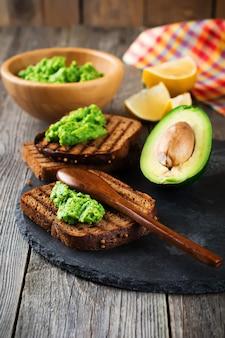 아보카도 전통 멕시코 소스, 아보카도와 레몬 오래 된 나무 표면에 샌드위치. 선택적 초점.