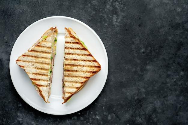 Бутерброды с ветчиной, сыром, помидорами, листьями салата и поджаренным хлебом в белой тарелке