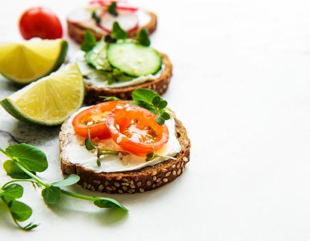 白いテーブルの上に健康的な野菜とマイクログリーンのサンドイッチ