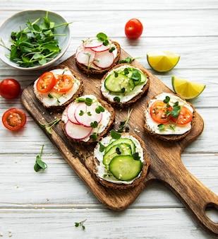 木製のテーブル、上面図に健康的な野菜とマイクログリーンのサンドイッチ