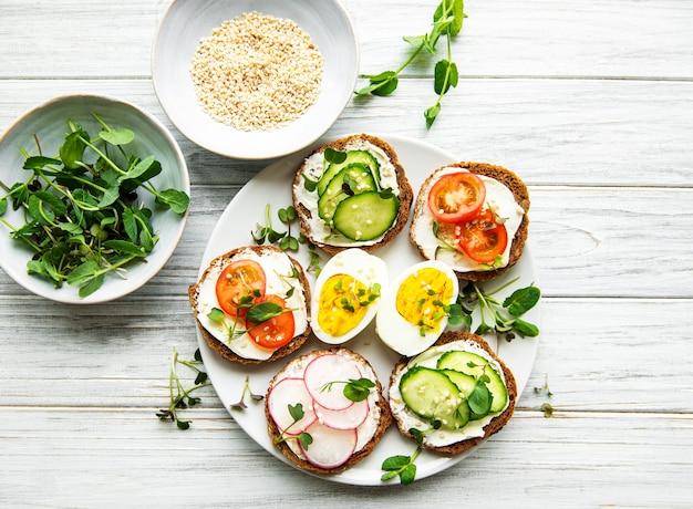 木製のテーブルに健康的な野菜とマイクログリーンのサンドイッチ