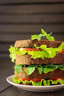 양상추와 루꼴라, 토마토와 오이를 곁들인 샌드위치, 신선한 야채를 곁들인 거친 짙은 빵의 비건 샌드위치