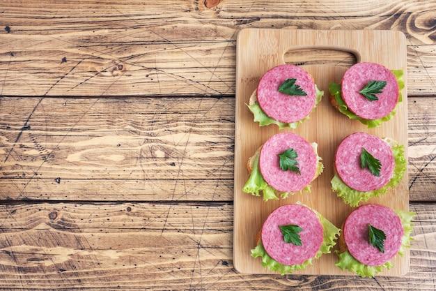 Бутерброды с листьями салата и нарезанной колбасой салями на деревянной доске. вид сверху