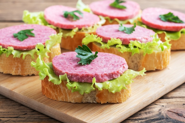 Sandwiches with lettuce leaves and sliced salami sausage on a wooden board.