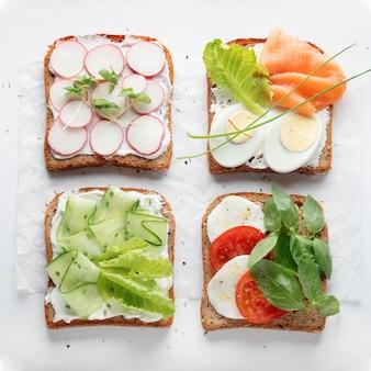 Sandwiches with mascarpone cheese, cucumber, radish, egg, caprese salad on a white wall.