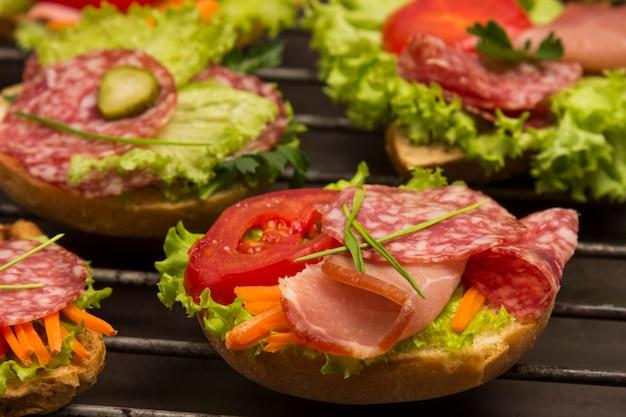 고기와 채소 샌드위치, 금속 그릴에 곡물 롤빵