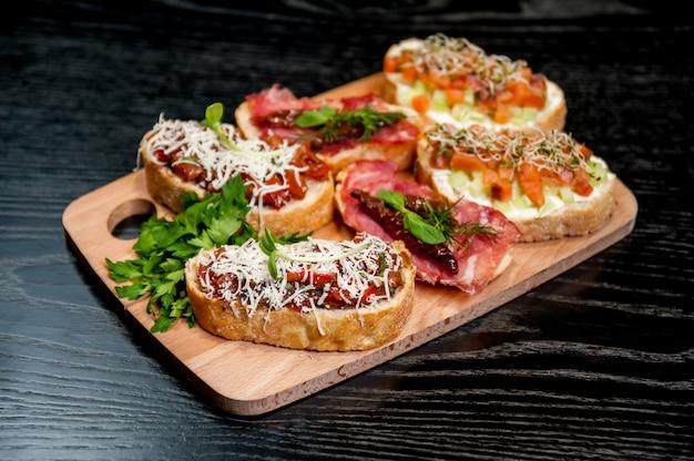 木製のテーブルで野菜と肉のサンドイッチ。