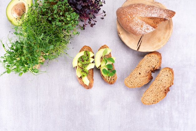 테이블에 마이크로그린과 아보카도가 있는 샌드위치. 깨끗한 음식 건강 식품 개념입니다. 위에서 보기