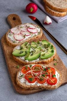 Sandwiches with microgreens and vegetables on a cutting board on a concrete surface